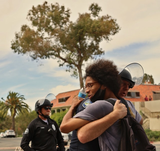 officer hugging citizen